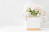 Mockup desk calendar and white peonies in a vase on a light background