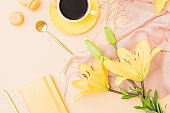Flat lay workspace with notebook, cup of coffee, yellow lilies and beige scarf on color background