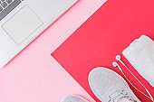 Home online workout concept. Flat lay sport shoes, new sneakers, laptop on a red background
