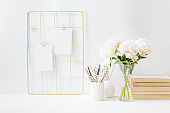 Home office desktop and mood board with empty card, white peonies in a vase, office supplies on a light background