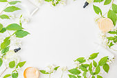 Flat lay composition with cosmetics and jasmine flowers on a light background