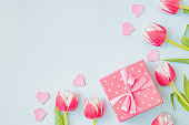 Flat lay valentines day frame with pink tulips and gift box on a light green background