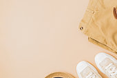Flat lay summer composition with a straw hat, denim and sneakers on a yellow background