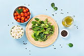 Healthy green salad preparation with salad leaves, tomatoes and mozzarella cheese on blue background