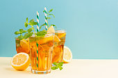 Traditional homemade iced tea with lemon, mint and ice in tall glasses. Summer cold drink concept.