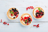 Homemade Tartlets with cream and fresh berries - ripe red and black currants, strawberries on blue rustic wooden background, top view.
