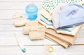 baby clothes and  attributes on a white wooden background. View from above