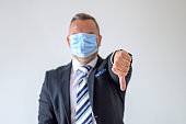 Businessman in face mask giving a thumbs down gesture