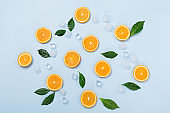 Natural healthy juicy organic orange slices and ice on blue background.