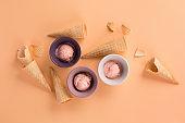 Homemade yogurt strawberry ice cream, sweet waffle cones on pastel pink background.