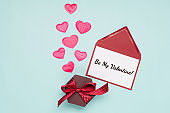 Pink textile hearts, empty card and gift box on blue background. Valentines day concept. Flat lay, top view, copy space.