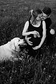 Young man hugs his pregnant wife, who is holding baby shoes in her hands, their smartest dog is lying next to her. Black and white photo. Waiting for child. Addition to family.
