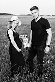 Young pregnant couple holds ultrasound image of their unborn child in their hands. Black and white photo. Waiting for child. Pregnancy management. Modern methods of examination.