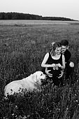 Young man expresses tenderness and care to his pregnant wife, who is holding children's shoes in her hands, their smartest dog is lying next to her. Black and white photo Funny moments.