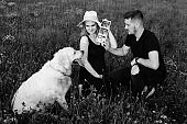 Owners show ultrasound photo to their dog, white Labrador.Black and white photo. Waiting for a child. Pregnancy management. Modern methods of examination.Happy moments .