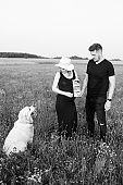 Pregnant young couple shows ultrasound of unborn child to their dog on walk on summer evening .Black and white photo. Pregnancy management. Modern methods of examination.