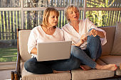 Two 55-year-old women in casual clothes use a laptop to shop online