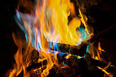 Burning campfire with colourful flames at night