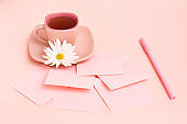 The concept is pink. Pink drink in a coffee cup, sheets for writing, a pen and a chrysanthemum on a pink background.