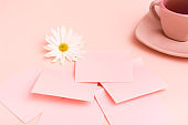 The concept is pink. A cup of coffee, sheets for writing, a pen and a chrysanthemum on a pink background.