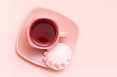 The concept is pink. Pink drink in a coffee cup and marshmallows on a saucer on a pink background. Top view