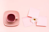 The concept is pink. Pink drink in a coffee cup, leaf for writing and chrysanthemum on a pink background. Top view
