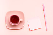 The concept is pink. Pink drink in a coffee cup, writing sheet and pen on a pink background. Top view