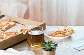Takeout food. A slice of pizza in a disposable plastic plate and a box of pizza on the table in the kitchen.