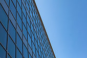 Glass facades of modern office buildings and reflection of blue sky and clouds. Facade design. Exterior for urban city background
