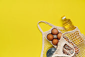 Eggs, pasta, canned food, oil in a string bag on yellow background. Copy space, flat lay. Crisis food stock for coronavirus quarantine isolation period. Food delivery, donation.