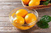 Fresh ripe lemons in a glass bowl with water on a wooden table