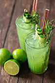Green ice cold tropical lime smoothie served with ice in two glasses