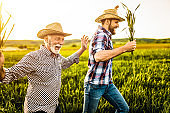 Two happy farmers running on an agricultural field.
