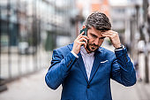 Worried businessman talking on phone.