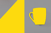 Illuminating and ultimate gray colors paper background - the fashionable colors of 2021 and an yellow mug on it.