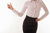 Girl in office clothes shows on a white wall.