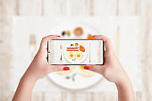 Taking photo of breakfast with phone. Woman holding smart phone in horizontal position