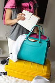 Elegant young brunette woman putting tablet pc and notepad diary into handbag ready to travel
