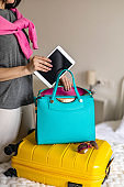 Woman hands ready travel journey putting tablet pc into handbag packing baggage at bedroom