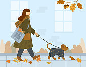Girl in a coat and with a scarf around her neck walks with dog down the autumn street. On the shoulder is a bag with colored leaves. A small dog in a grey jumpsuit.