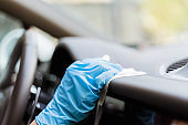 Hands wearing gloves cleaning and disinfecting car interior