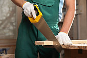 Professional carpenter cutting wooden board with handsaw in workshop, closeup