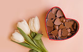 Gifts for the holiday. White tulips and chocolate on pink background