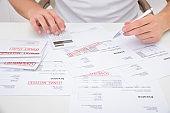 Close-up Of A Man Calculating Unpaid Bills Using Calculator