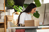 Woman sitting at her desk and preparing packages for her customers