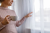 Midsection of woman enjoying tea by the window and looking outside