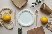 Eco-friendly disposable organic utensil. Knives, forks, empty plate, string bag and paper bag and inscription zero waste from wooden letters. Zero waste concept. Ecology concept. Top view, flat lay