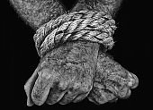 Man's hands, bound by thick rope, against black background