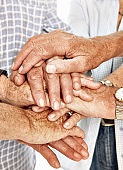 Group of senior men and women stack their hands in solidarity, love and unity