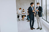 Two young business men with facial protective masks discussing  with paper plan in the office